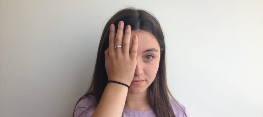 CHECT Photo - a young person with her hand over one eye