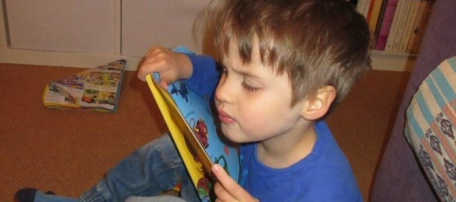 CHECT photo - a young boy reading a book