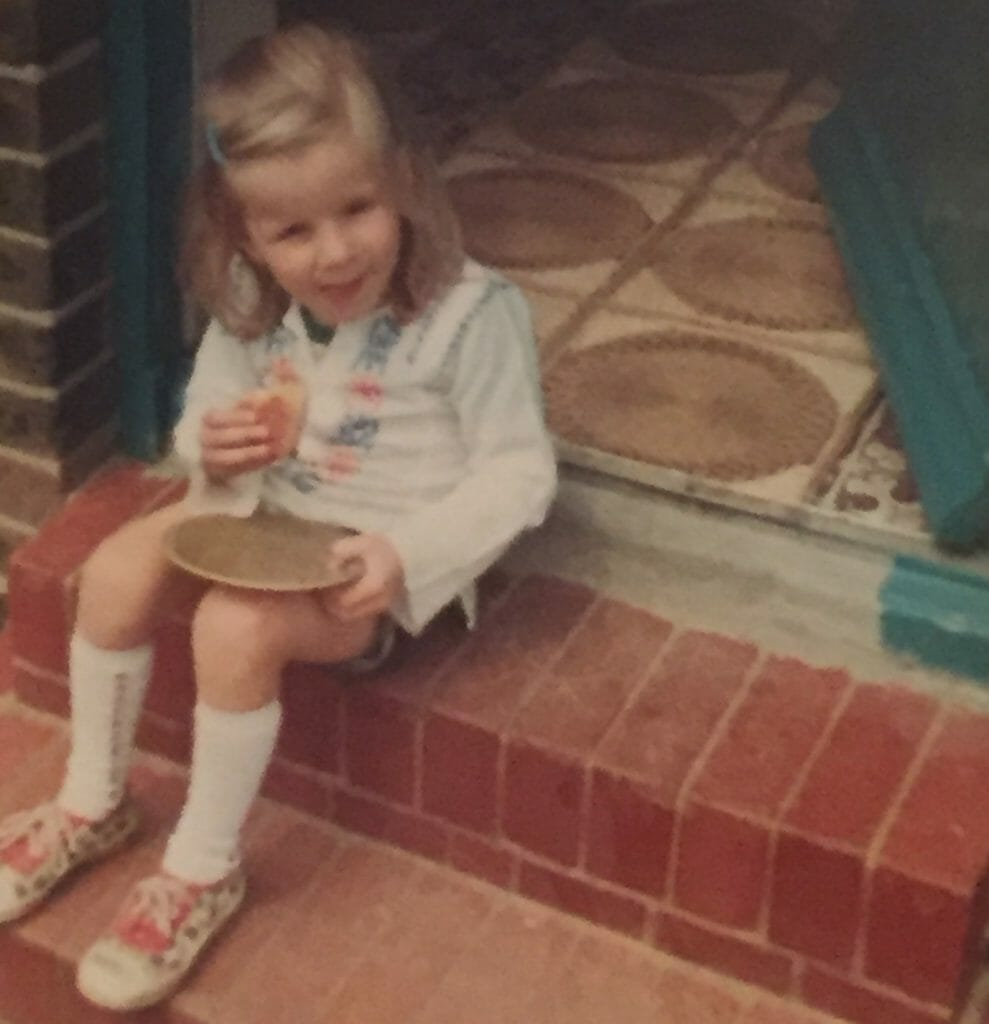 CHECT photo - Zoe Weeks as a girl, sitting on a step eating some food