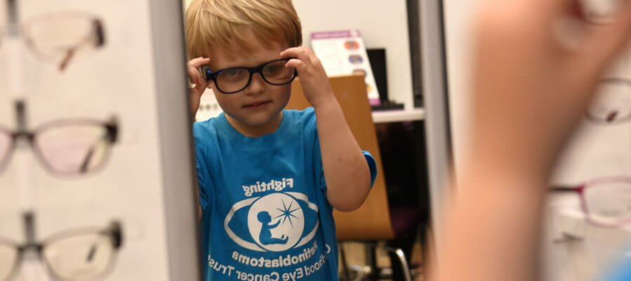 CHECT photo - Ethan Warman, a young CHECT ambassador, trying on glasses at the Vision Express store in Redditch