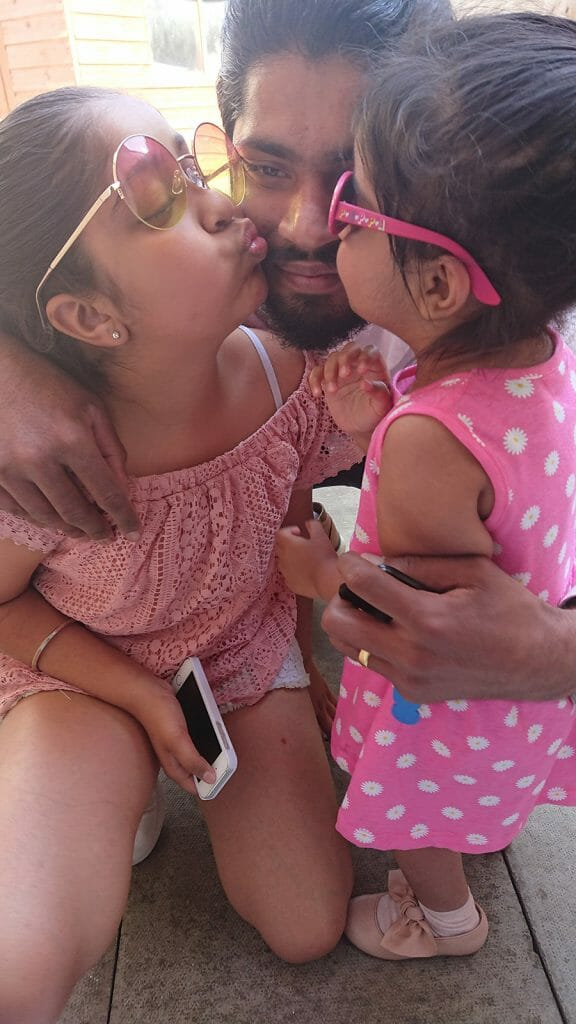 CHECT photo - Kulvir with his two daughters, they are both kissing one of his cheeks