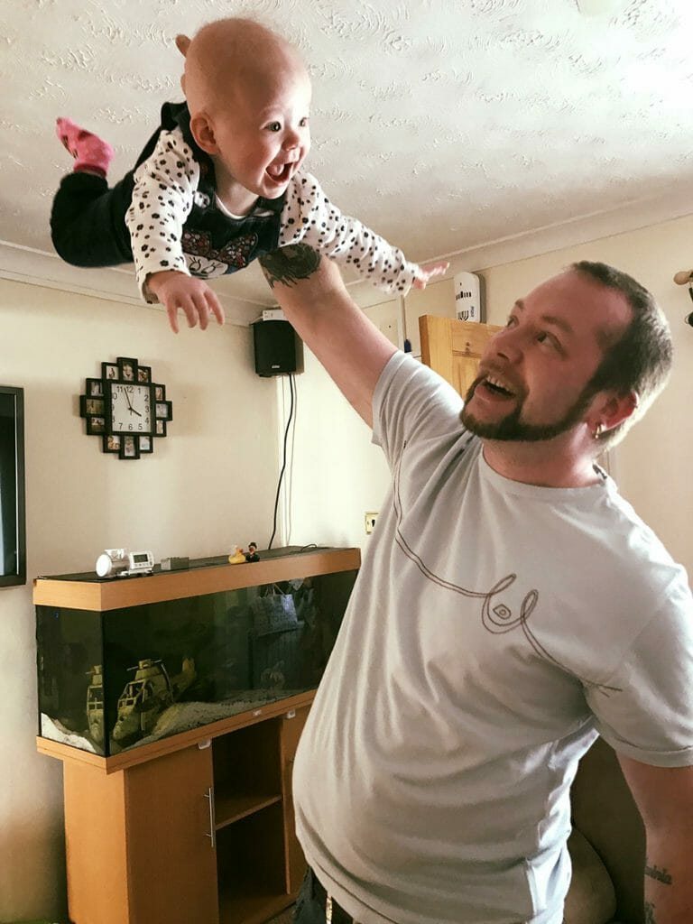 CHECT photo - Steve Crosbie throwing his daughter Lavinia up into the air, she is laughing