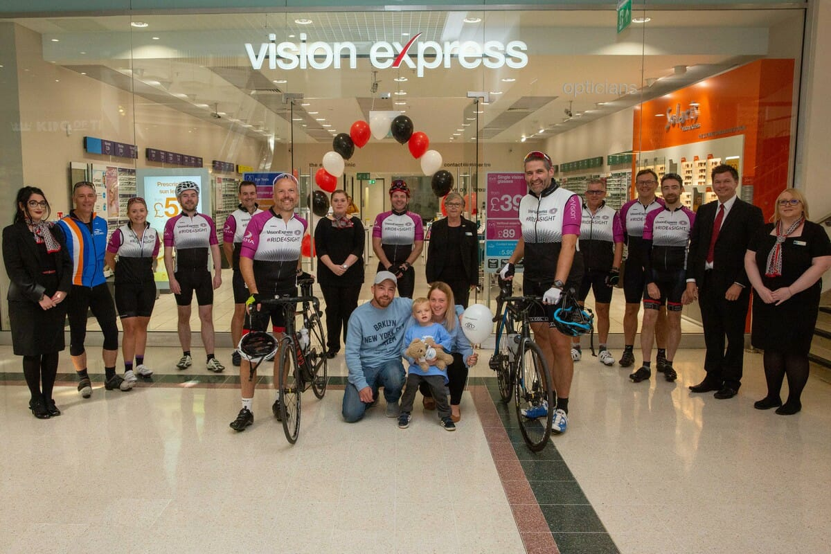 Photo of the cyclists outside a Vision Express store