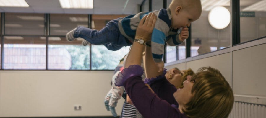 Photo of a mum throwing her young son into the air and smiling up at him