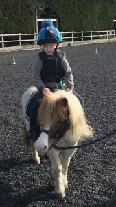 James riding a pony in an outdoor arena. The horse is being lead by someone off camera.