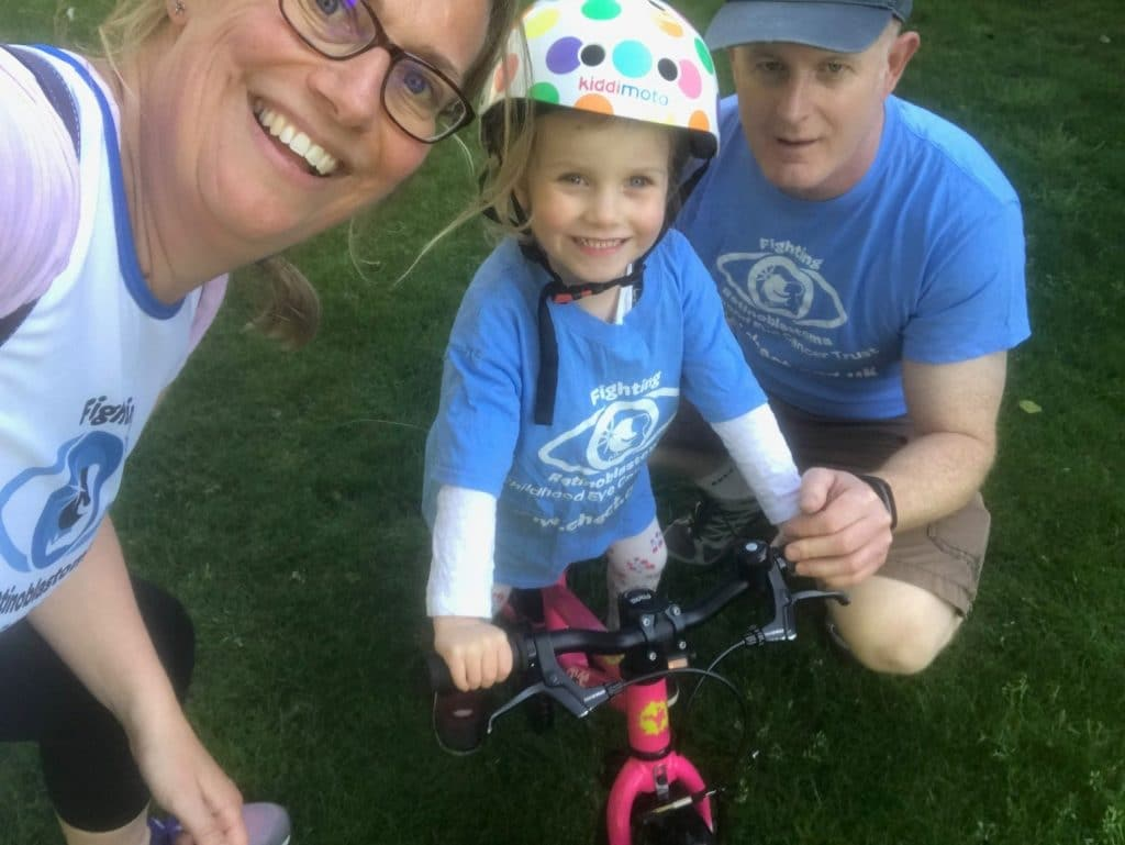 Amber, mum Pippa and Dad Glenn all wearing CHECT Tshirts. Pippa is riding her bike.