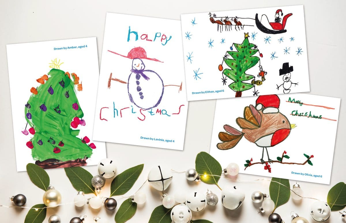 A photo showing the four Christmas card designs amongst white bells, fairy lights and leaf decorations