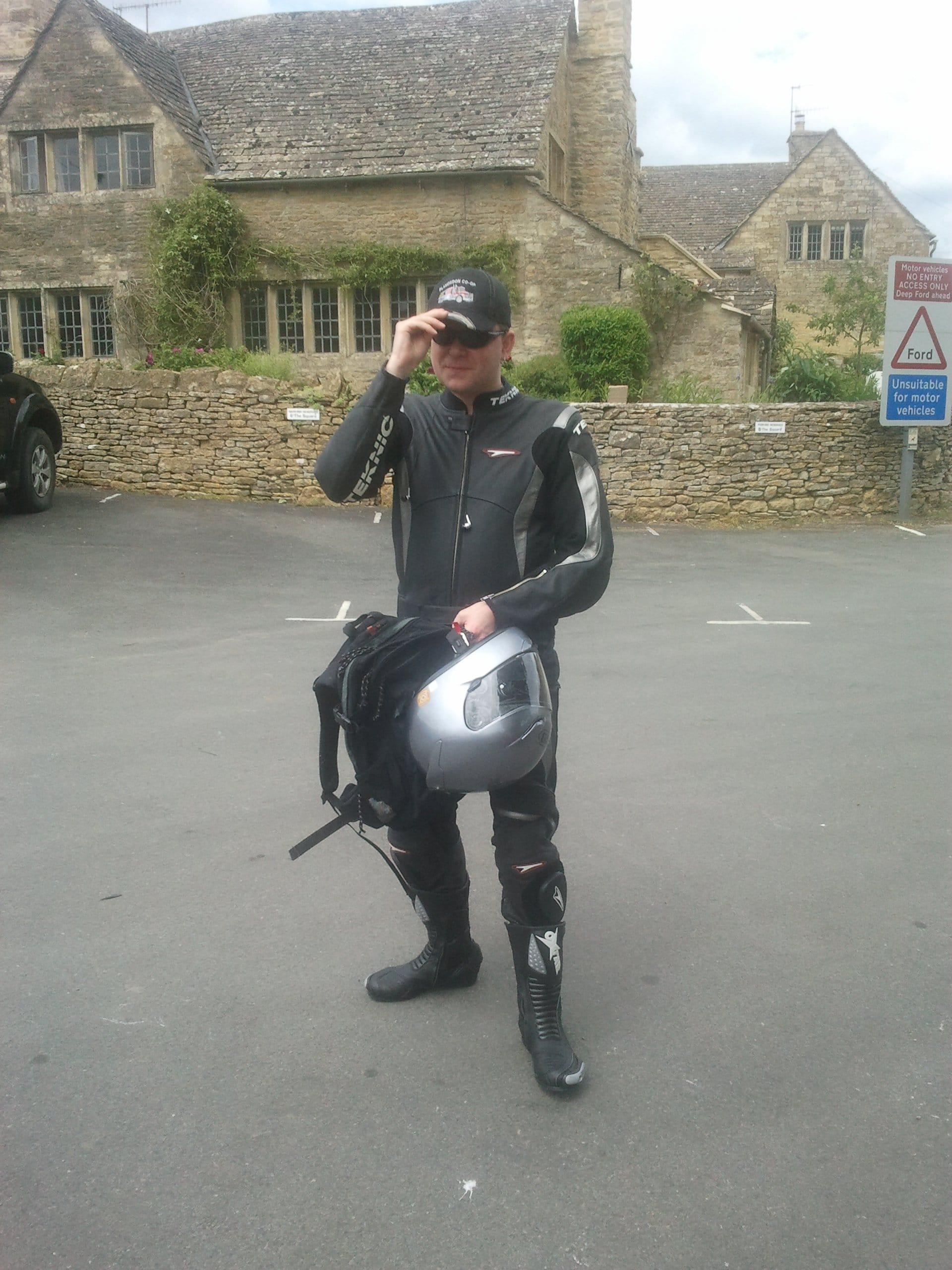 Iain Riddell holding his motor cycle helmet