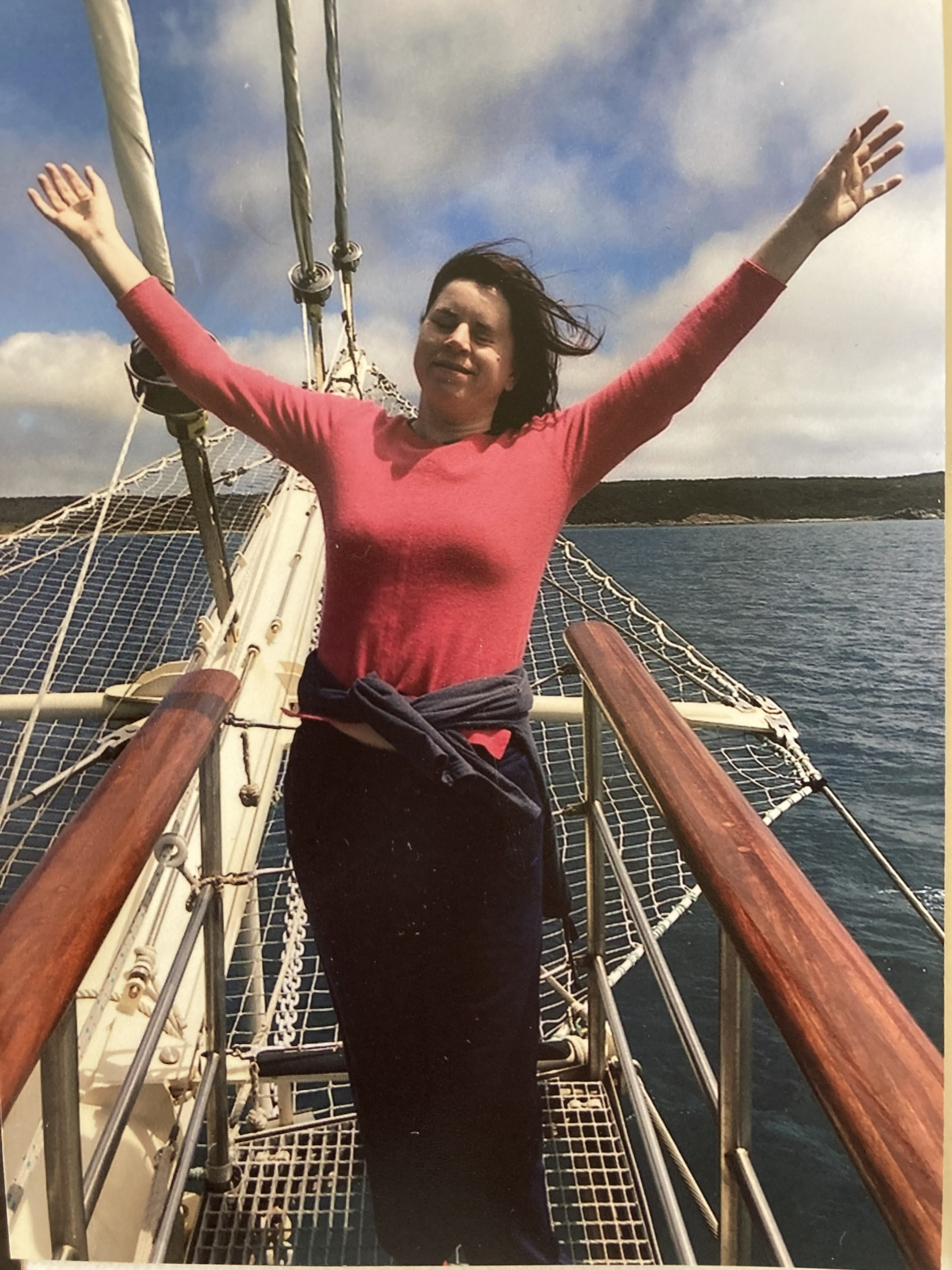 Ffion on a boat in the ocean, smiling and standing with her arms stretched outwards towards the sky.