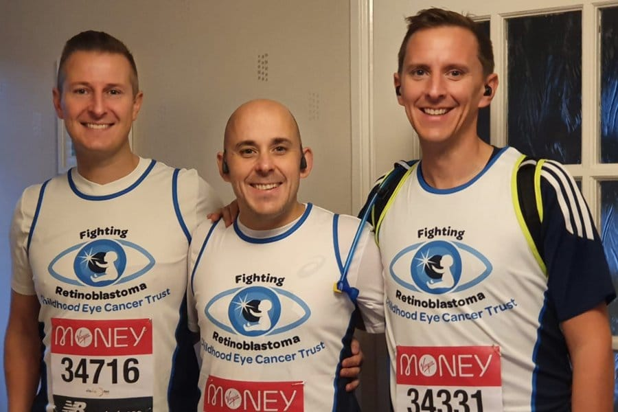 Three men posing for a photo in the CHECT vests before they complete the virtual london marathon.
