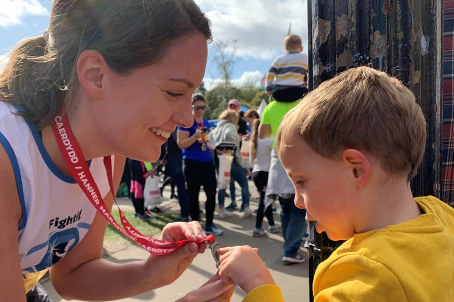 A mother showing her son the medal she won in Cardiff raising money for CHECT