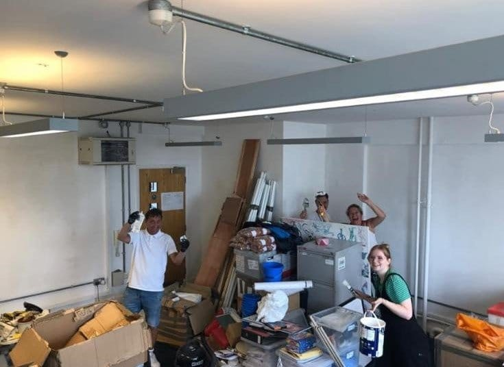 A photo of Beth and volunteers moving the CHECT office