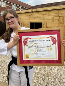 Olivia receives her black belt certificate in taekwondo