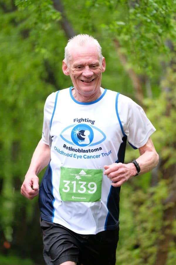Daniel Pincham-Phipps running through the countryside with his CHECT running vest on